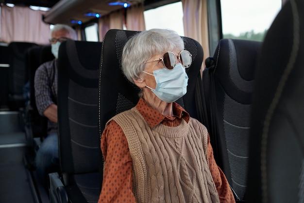 Старшая кавказская дама с седыми волосами в солнцезащитных очках и маске для лица сидит в автобусе