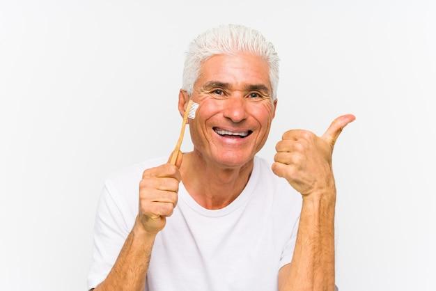 笑みを浮かべて、親指を上げる分離された歯ブラシを保持している年配の白人男性