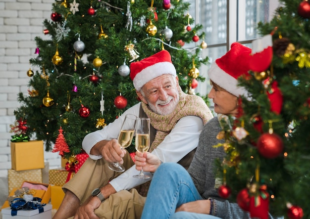 Senior caucasian man holding and cheers champagne flute together with his wife between decorated christmas tree in cozy living room in winter. lover couple with santa hat. celebrate merry christmas.