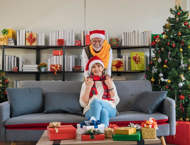 贈り物とクリスマスで飾られたリビングルームで笑顔の幸せそうな顔で後ろからソファのソファに座っている彼の妻の手を握っている年配の白人男性。ロマンスは休日のカップルをリラックスさせます。