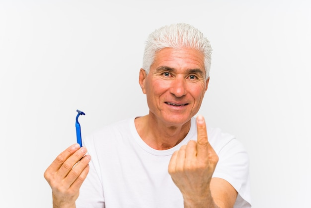 Senior caucasian man holding a razor blade isolated pointing with finger at you as if inviting come closer.