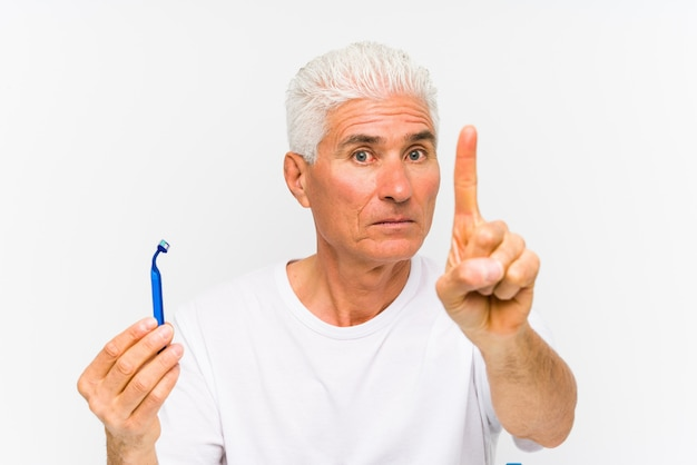 Senior caucasian man holding a razor blade isolated ã§showing number one with finger.