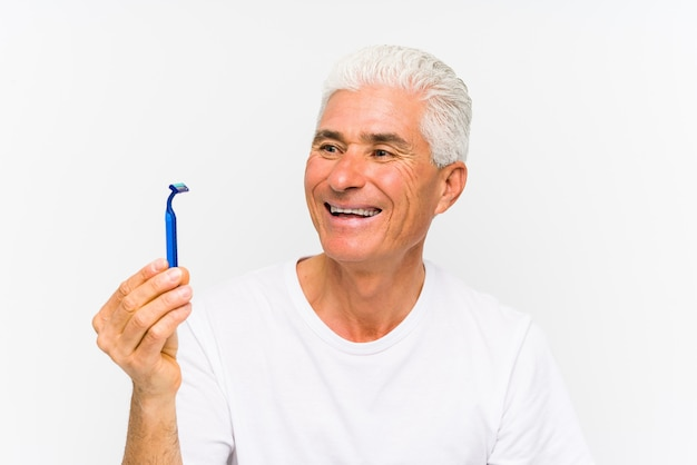 Senior caucasian man holding a razor blade isolated ãƒâ§smiling confident with crossed arms.