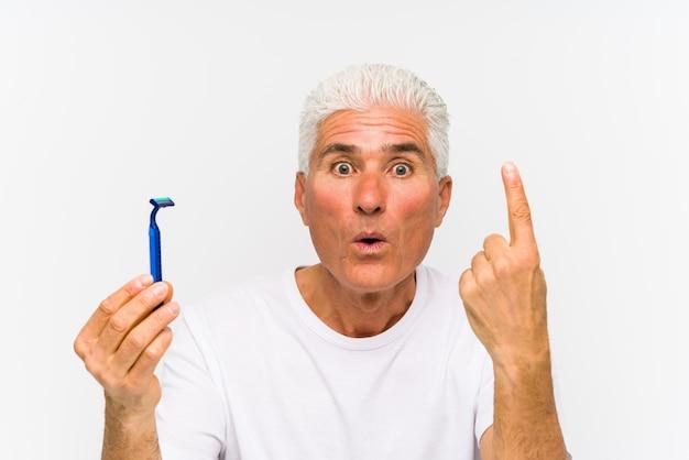 Senior caucasian man holding a razor blade isolated