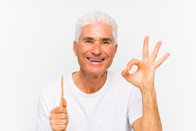 Senior caucasian man holding a teethbrush isolated cheerful and confident showing ok gesture.