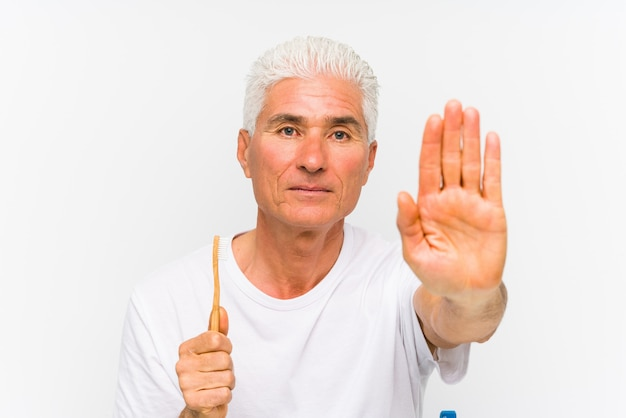 Senior caucasian man holding a teethbrush isolated standing with outstretched hand showing stop sign, preventing you.
