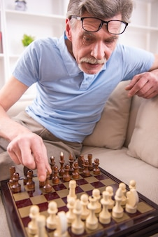 年配の白人男性は男の子とチェスをしています。