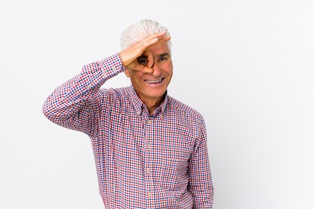 Senior caucasian man isolated excited keeping ok gesture on eye.