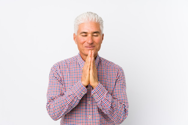 Senior caucasian man isolated holding hands in pray near mouth, feels confident.