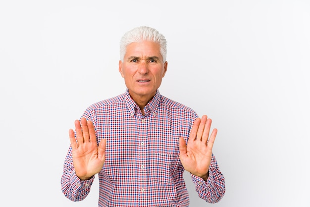 Senior caucasian man isolated rejecting someone showing a gesture of disgust.