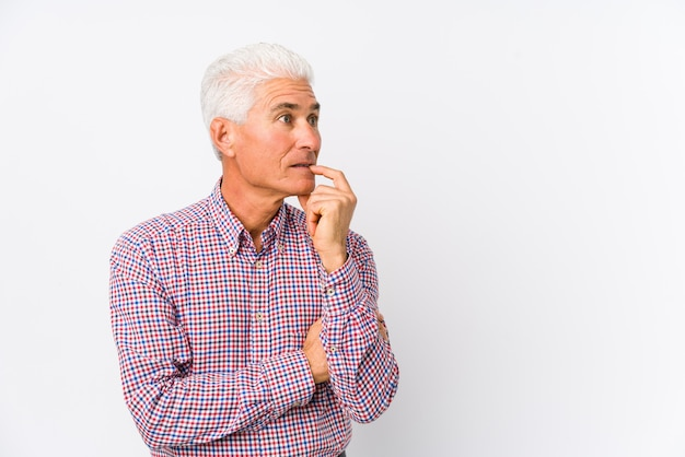 Senior caucasian man isolated relaxed thinking about something looking at a copy space.