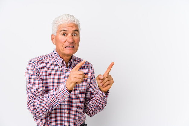Senior caucasian man isolated shocked pointing with index fingers to a copy space.