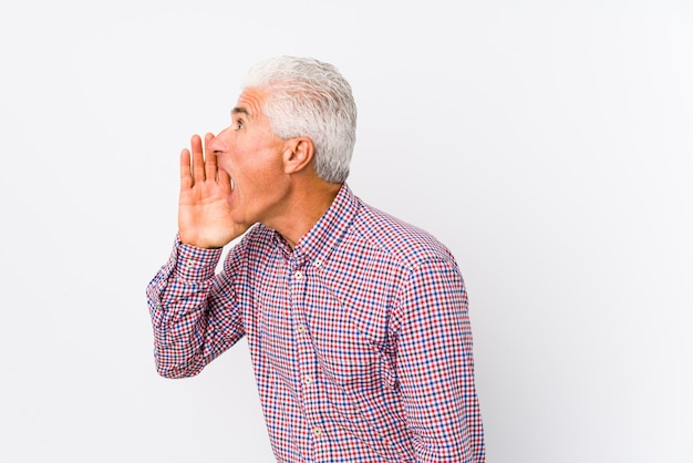 Senior caucasian man isolated shouting and holding palm near opened mouth.