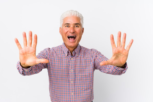 Senior caucasian man isolated showing number ten with hands.