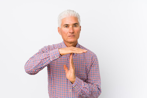 Senior caucasian man isolated showing a timeout gesture.