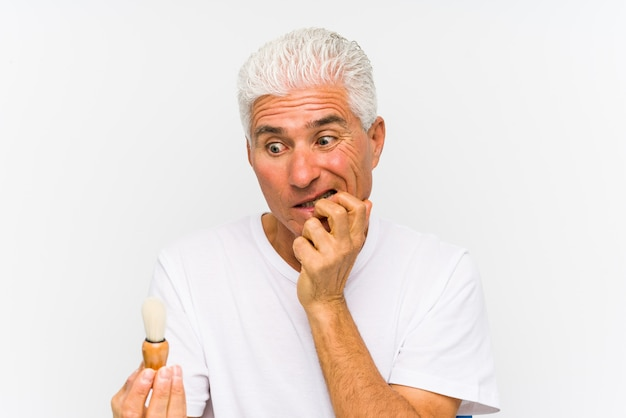 Senior caucasian man recently shaved biting fingernails, nervous and very anxious.