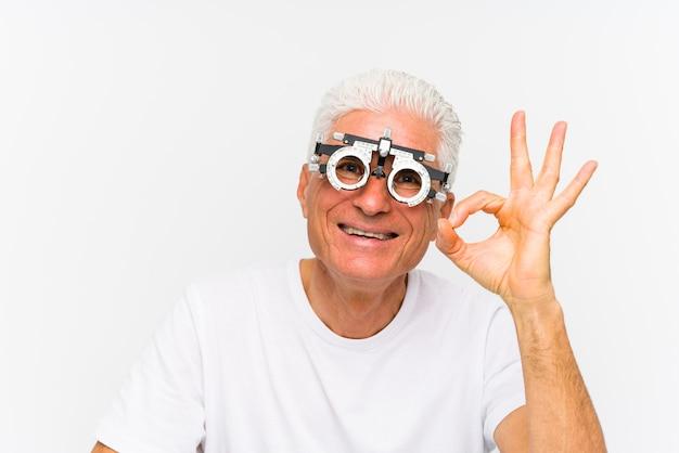 Старший кавказский человек нося рамку пробного оптометриста жизнерадостную и уверенно показывая одобренный жест.