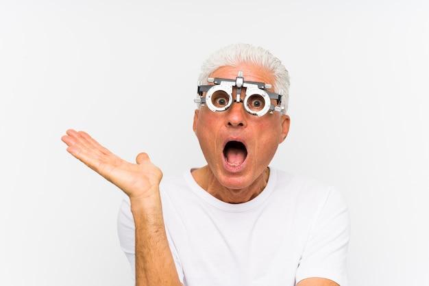 Старший кавказский человек нося рамку optometrist пробную впечатил держащ космос экземпляра на ладони.