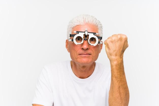 Старший кавказский человек нося рамку optometrist пробную показывая кулак к с агрессивным выражением лица.