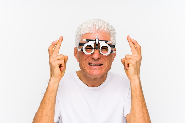 Senior caucasian man wearing a optometrist trial frame crossing fingers for having luck