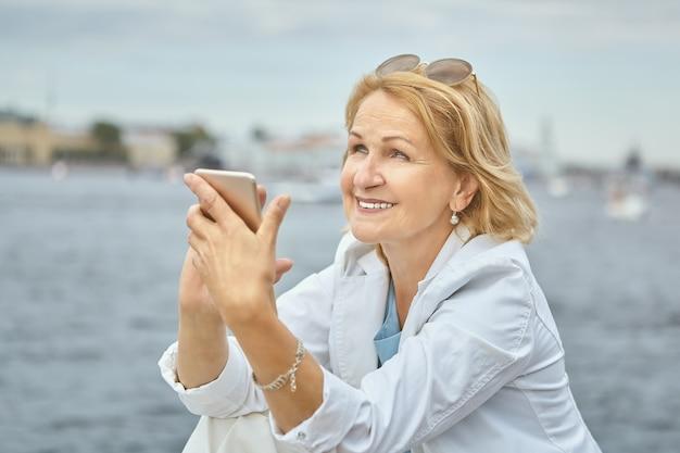 60 세 수석 백인 꽤 웃는 아가씨 손에 스마트 폰으로 시내 지역을 걷는 동안 강가에 서 있습니다.