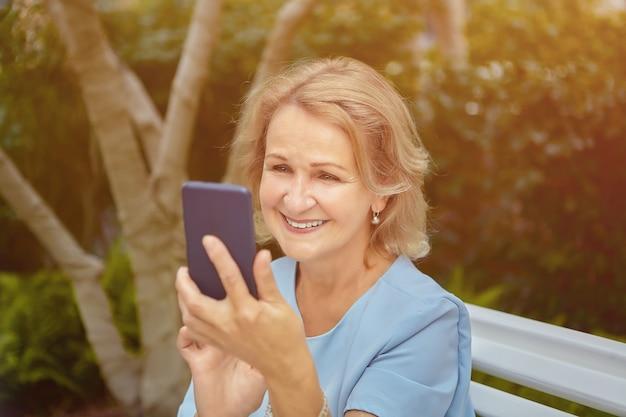 수석 백인 예쁜 여자는 웃 고 행복 한 얼굴로 그녀의 스마트 폰에서 찾고 있습니다.