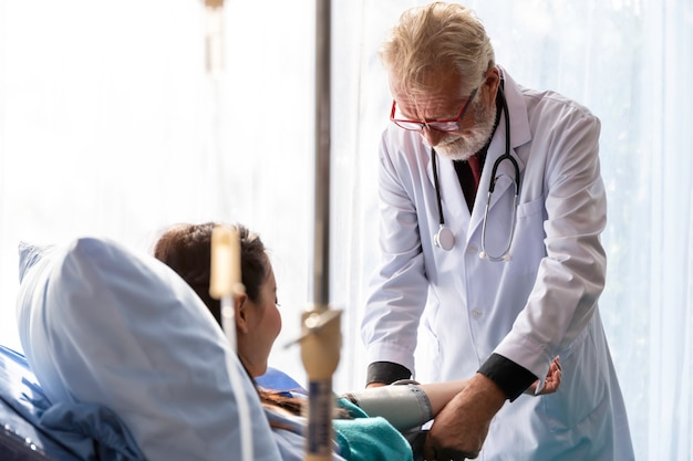Senior caucasian professional doctor man check blood pressure with asian woman patient in the hospital room.