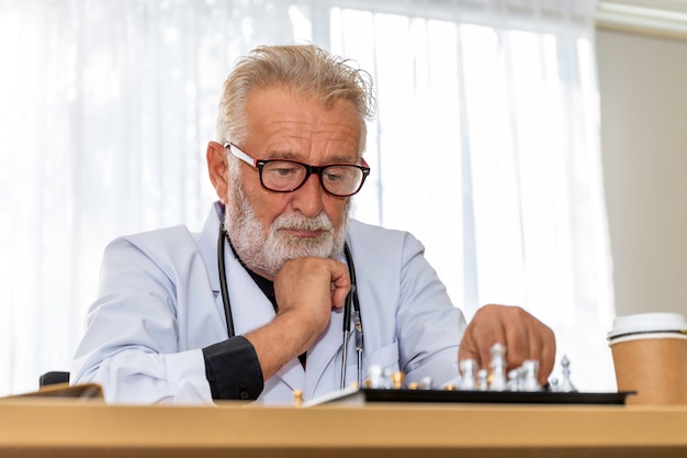 Senior caucasian serious man doctor headache resting and playing chess in room.