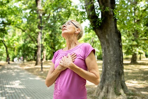 달리기 훈련 중에 가슴 통증이나 심장마비를 겪는 백인 노인 여성.