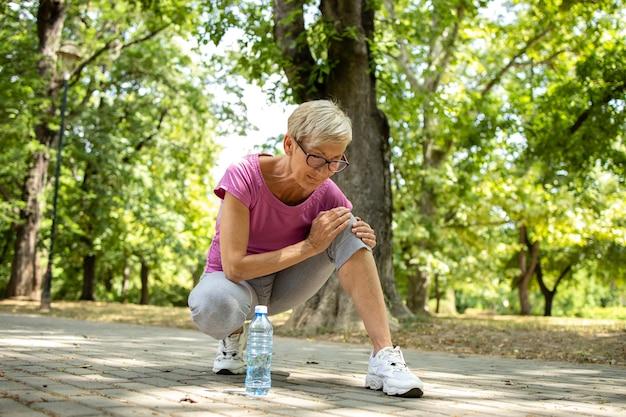 Старшая кавказская женщина, имеющая боль в колене во время тренировки.