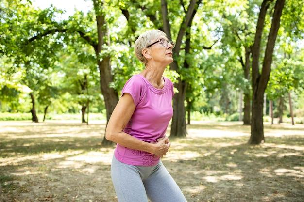 훈련을 실행하는 동안 복통이 수석 백인 여자.