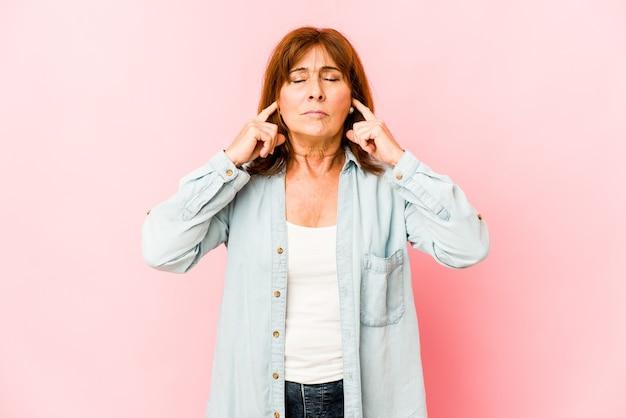 수석 백인 여자는 손가락으로 귀를 덮고, 스트레스와 시끄러운 주변에 의해 필사적입니다.