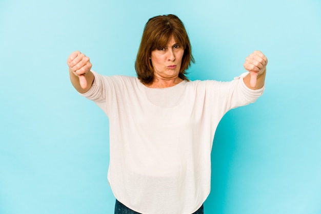 Senior caucasian woman isolated showing thumb down and expressing dislike.