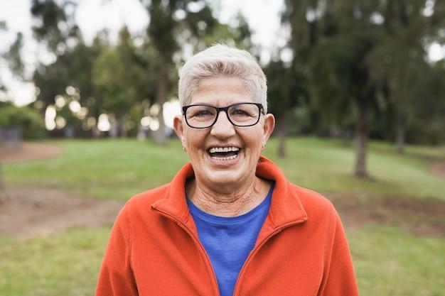 都市公園で屋外のカメラに笑みを浮かべて年配の白人女性