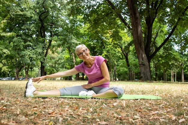 그녀의 다리를 스트레칭, 워밍업 및 자연에서 달리기 훈련을 준비하는 수석 백인 여성.