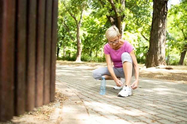 공원에서 조깅하기 전에 그녀의 신발끈을 묶는 수석 백인 여자.
