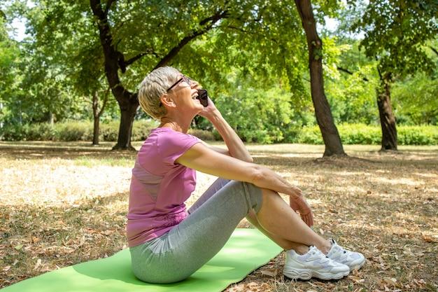 スマートフォンを使用し、トレーニング休憩で彼女のトレーナーと話している年配の白人女性。
