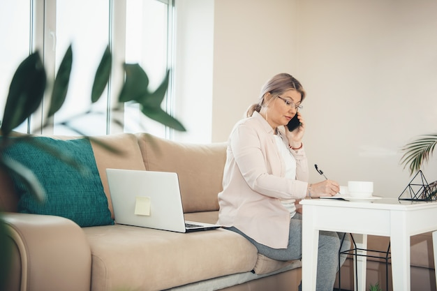 Старшая кавказская женщина со светлыми волосами и очками работает из дома за компьютером, пока что-то пишет