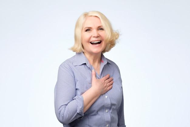 ブロンドの髪が笑っている年配の白人女性