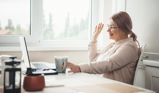 Старшая кавказская женщина в очках пьет чай и улыбается ноутбуку, показывая привет
