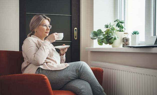 肘掛け椅子に座って、眼鏡をかけ、ラップトップでレッスンを見ながらコーヒーを飲む眼鏡をかけた年配の白人女性