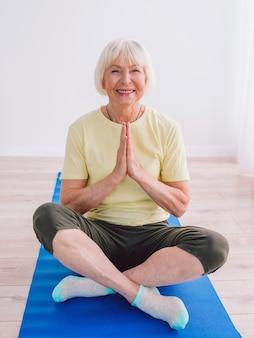 Senior cheerful peaceful woman doing yoga indoor namaste hands anti age sport yoga concept