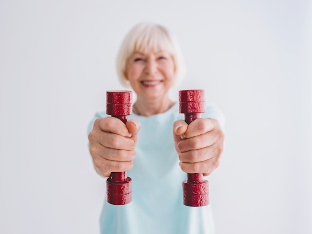 ダンベルでスポーツをしている年配の陽気な女性アンチエイジスポーツ健康的なライフスタイル