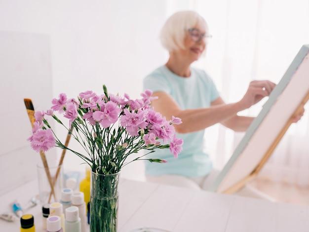 Старший жизнерадостная женщина в очках с седыми волосами картина натюрморт творчество искусство хобби