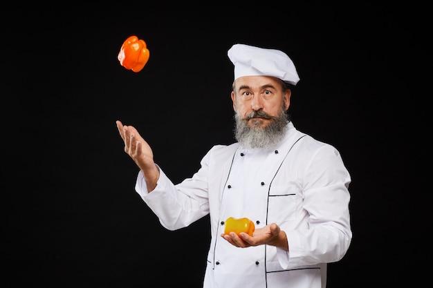 Senior chef juggling vegetables