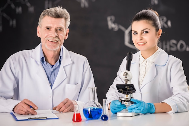 Senior chemistry professor and his assistant work.