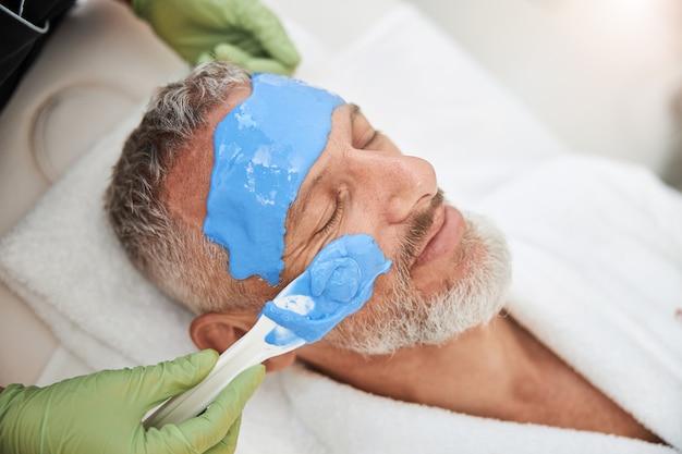 파란색 얼굴 거품으로 얼굴을 덮는 동안 스킨 케어 절차를 즐기는 노인