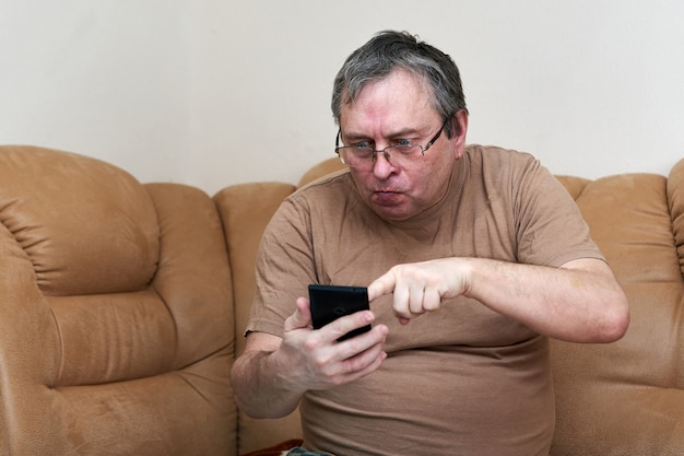 Senior citizen sitting on the couch understands the gadget mastering smartphone
