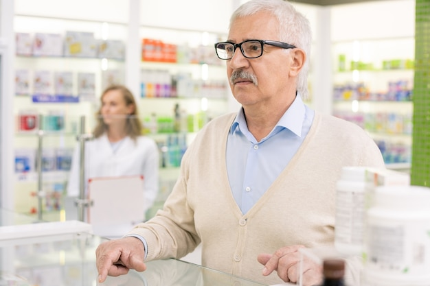 Старший клиент современной аптеки стоит у прилавка и ждет, пока фармацевт посоветует ему, какое лекарство купить