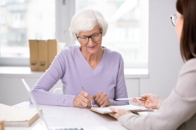 Senior client putting her signature in insurance agreement after discussion of its terms and conditions with agent at meeting